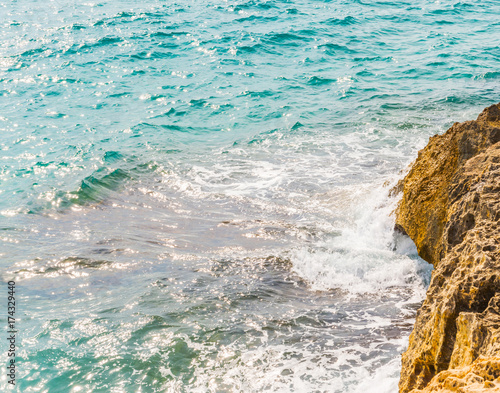 Staande foto Lichtblauw high cliff above the sea, summer sea background, many splashing waves and stone
