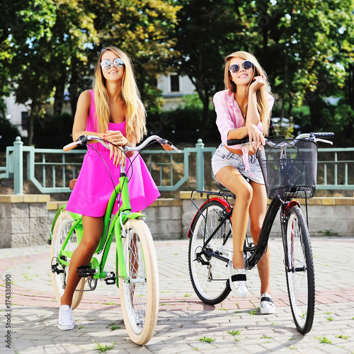 Two girls on a bicycles - outdoor summer portrait