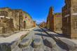 Quadro Italy. Ancient Pompeii (UNESCO World Heritage Site). Paving stones of Via Stabiana (Cardo Maximus street) with the blocks stone. There is Mount Vesuvius in the background