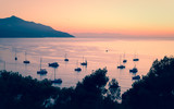 Private boats and small yachts anchored in a quiet bay in the Italian Mediterranean sea at sunset. Vintage effect.