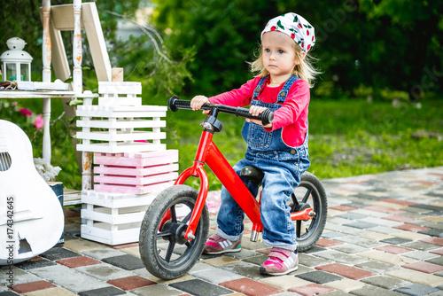 little girl riding her red bike
