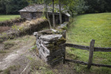 ancient rustic stone made house and a fence in the woods - 174347268