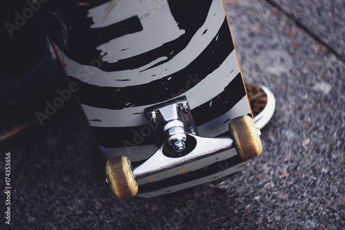 The legs of a guy in sneakers with a skateboard on the street. Close-up of skate wheel and suspension