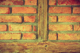 Red brick wall with wooden pieces