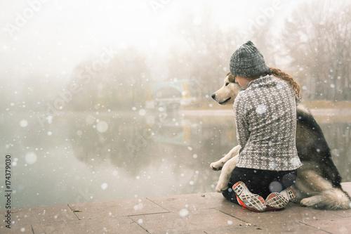 Image of young girl hug her dog, alaskan malamute, outdoor