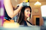 Woman getting her hair dried at the hair salon - 174406454