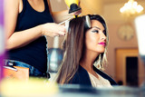 Hairdresser dries hair with a hairdryer in beauty salon - 174406493