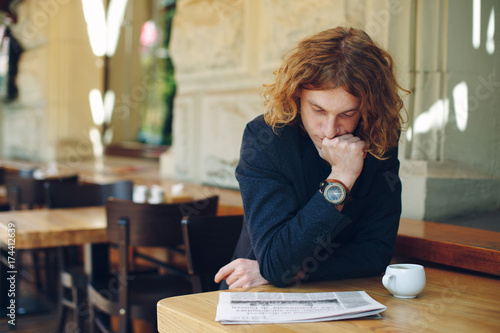 Young entrepreneur reading newspaper in a cafe
