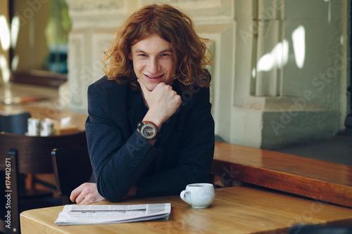 Young reddish man smiling touching his chin