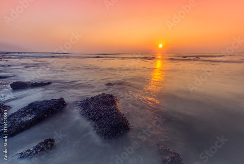 Aluminium Koraal Tropical sunset on the stones beach.