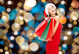 woman in santa hat with christmas shopping bags