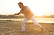 Athletic capoeira performer making movements on the beach