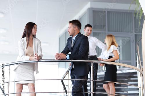 Business people having break and talking on terrace of office building.