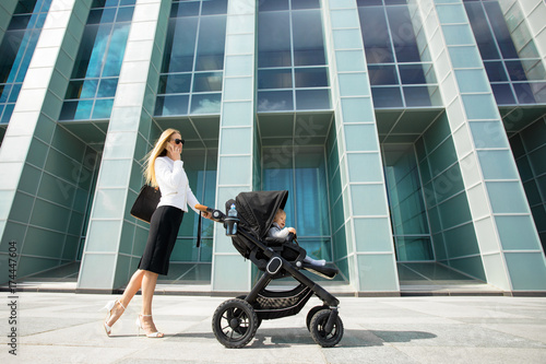 Mother and business woman talking on the phone while going to work Poster