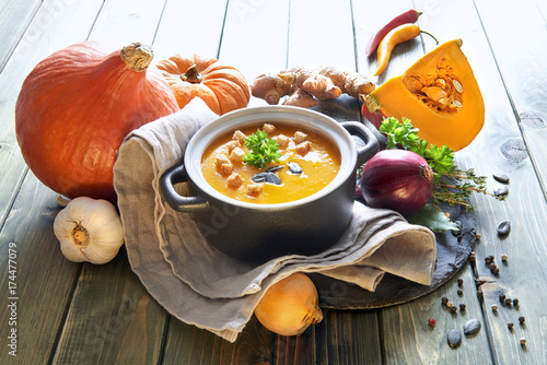 Spicy pumpkin creme soup with carrot and chili pepper on wood