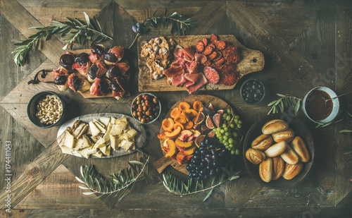 Flat-lay of holiday, party, family dinner table set with wine snacks. Meat, cheese, olives, crostini sandwiches, prosciutto, bread over wooden background, top view. Fingerfood or catering food concept
