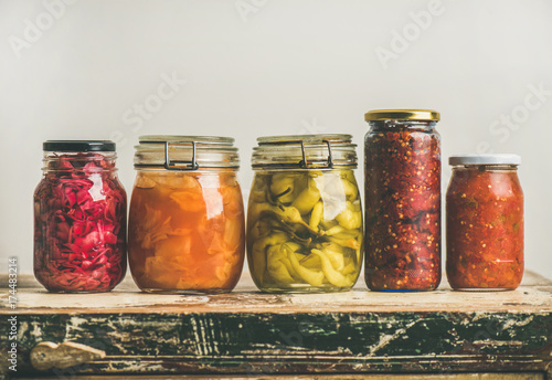 Autumn seasonal pickled or fermented colorful vegetables in jars placed in row over vintage kitchen drawer, white wall background, copy space. Fall home food preserving or canning