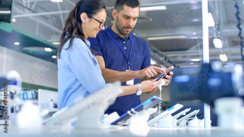 In the Electronics Store Consultant Gives Professional Advice to a Young Woman, She Considers Buying New Tablet Computer and Needs Expert Opinion. Store is Modern, Bright and Has all the New Devices.