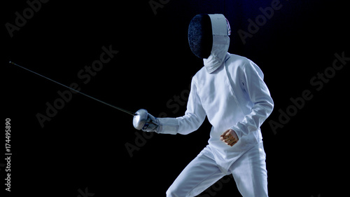 One Professional Fencer is Standing Ready for Fighting. Shot Isolated on Black Background with Cold Tones.
