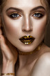 beautiful girl with a golden shiny make-up and stars on her lips. Beauty face. Photo taken in the studio.