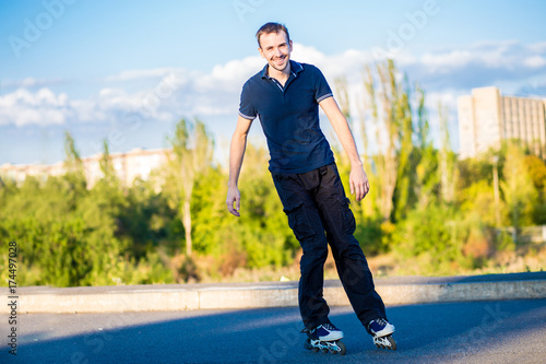 Happy young man rollerblading in city park at sunset Poster
