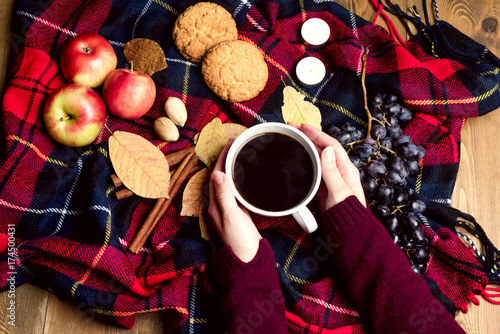 Papiers peints Bordeaux Hand keeping cup of coffee Apple Cookies Cinnamon Grape Wooden background Autumn blanket Autumn lifestyle concept Top view