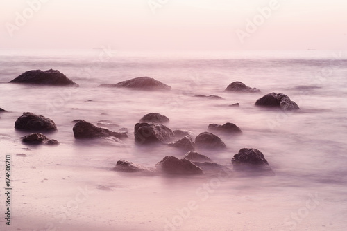 Foto op Aluminium Lichtroze Summer seasonal natural vacation background. Romantic morning at sea. Big boulders sticking out from smooth wavy sea. Long exposure.