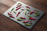 Red and green chili pepper on a stone slate board - 174520203