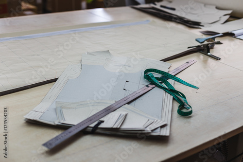 Still life photo of a clothes pattern template with ruler, tape measure on table. Sewing and tailoring tools and accesories.