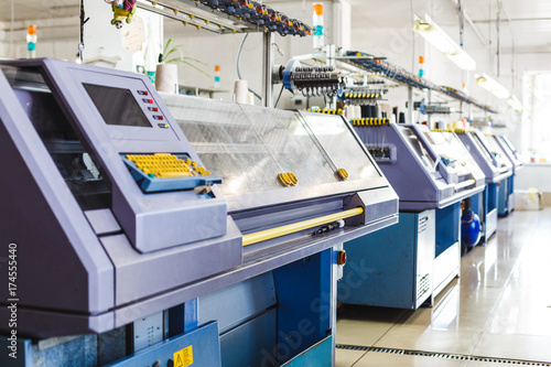 Textile industry with knitting machines in factory. Knitting and weaving machines in textile industry - 174555440