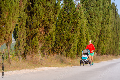 Poster Jogging Running mother with stroller enjoying motherhood at sunset landscape