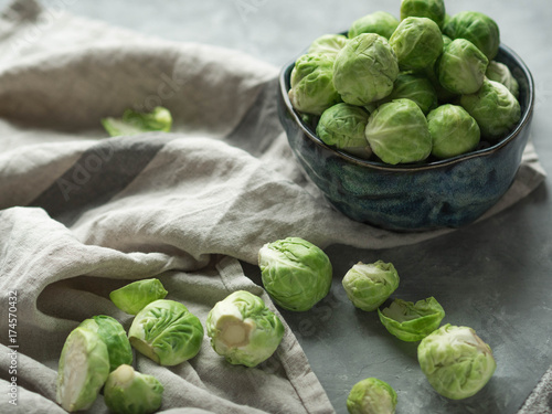Papiers peints Bruxelles Fresh Brussels sprouts in a blue bowl and scattered next to a gray linen towel on a gray textured background