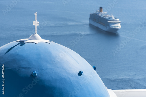 Santorini, the typical blue dome of Orthodox church and in the background a large cruise ship in the Aegean Sea
