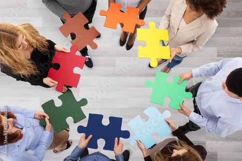 Papiers peints Echelle de hauteur Group Of Business People Holding Colorful Jigsaw Puzzles