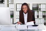 Confident Businesswoman Calculating Tax At Desk - 174667068