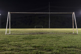 Empty soccer field at night through goal without net
