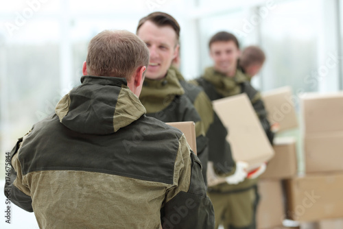 Happy male movers in uniform carrying boxes