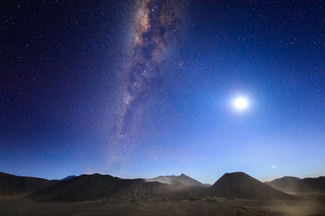 Bromo volcano with milky way, the moon and sand strom Tengger Semeru national park, East Java, Indonesia
