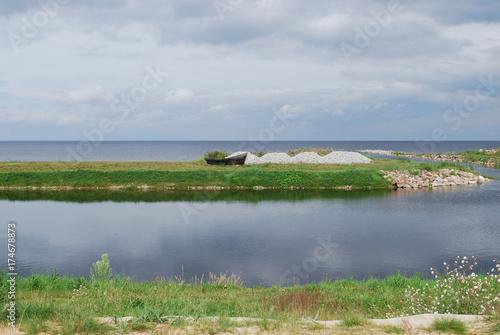 Wooden boat on the Lake Peipsi (Chudskoe lake) shore, overcast. Estonia landscapes.