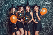 Beautiful girls in witches costumes on a dark background with a picture. Halloween.