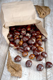 Chestnut package wooden table scattered brown fruit leaves withered - 174690436