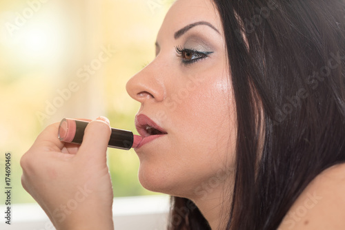 Young woman applying pink lipstick, light effect Poster