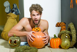 Halloween macho with open mouth, pumpkins and striped stockings - 174693476