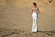 Woman or girl in white sexy dress standing in dunes
