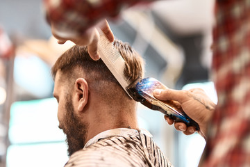 Professional barber making a hairdo with a electric razor