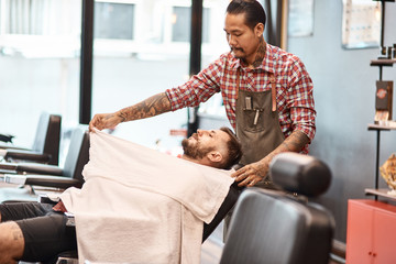 Professional thai barber putting a cape on his bearded client