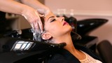 Beautiful young woman with hairdresser washing head at hair salon - 174705294