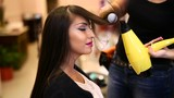 Hairdresser dries hair with a hairdryer in beauty salon - 174705828