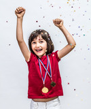 Successful beautiful child laughing with champion medals, celebrating over confettis - 174705837