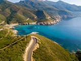 Vista aerea della costa della Corsica, strade serpeggianti e calette con mare cristallino. Penisola di Cap Corse, Corsica. Tratto di costa. Anse d'Aliso. Golfo d'Aliso. Francia - 174717066